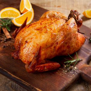 Roasted chicken with spices on wooden background, selective focus. Healthy food, diet or cooking concept
